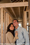 New home construction stock photo of a smiling happy hispanic couple visiting the new house they are having built.
